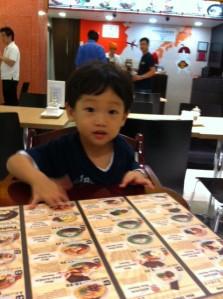 Toddler reading Asian menu