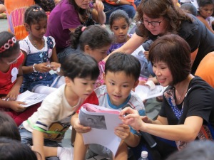 Dr Amy Khor reading with children offstage